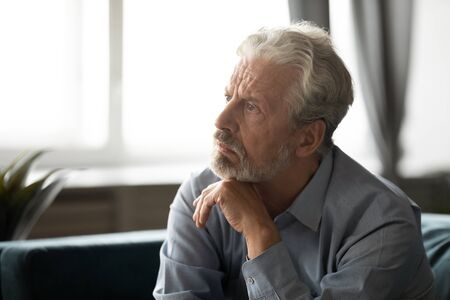Pensive depressed elderly male look in distance thinking pondering at home, thoughtful unhappy mature man lost in thoughts feel lonely abandoned, mourn or yearn, old people solitude concept