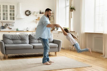 Overjoyed young dad have fun feel playful engaged in funny game with cute little preschooler daughter, happy father playing with small girl child, enjoy family weekend at home together