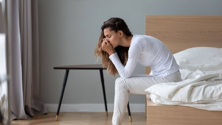 Depressed millennial girl sit on bed in home bedroom thinking pondering suffering from depression, upset unhappy young woman lost in thoughts struggle with relationship problem or psychological drama