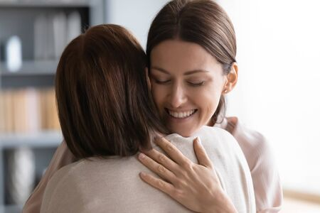 Head shot close up affectionate young woman embracing middle aged brunette mother, feeling thankful. Loving grownup daughter cuddling senior older mommy, greeting at home, missing after separation. Imagens