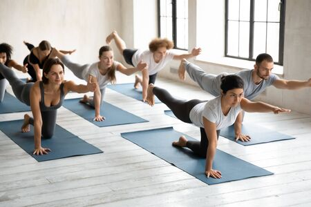 Young attractive Indian ethnicity woman lead yoga class, group of multi-ethnic people wearing sportswear performing Bird Dog Asana, work out process, grey colors, spacious light room, wellness concept