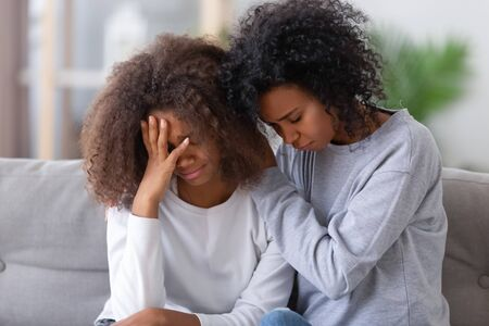 Upset african american mom sister hugging sad child teen girl consoling supporting or asking for forgiveness after fight, black mother hugging comforting depressed teenage daughter sitting on sofa Stock Photo