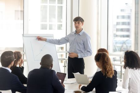 Male businessman draws graphs on flip chart at client presentation. Mentor coach talking business report with corporate diverse group at boardroom, leader consulting new project at negotiation room