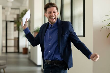 Happy millennial male employee dance in office corridor celebrate end of week or have Friday fun, overjoyed young man worker have fun feel excited after successful project startup good result