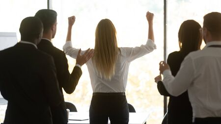 Rear view young female professional standing near window, raising hands, celebrating company success victory, multiracial group of colleagues supporting applauding congratulating with achievement. Reklamní fotografie
