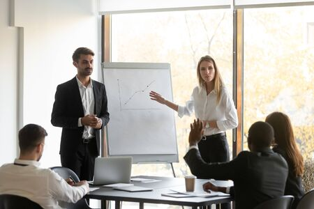 Two young confident female and male speakers trainers holding educational seminar, standing near flipchart with graphs, answering to employees clients investors questions about growth strategy. Standard-Bild