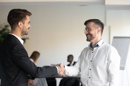 Two smiling business partners shaking hands with each other, celebrating good profitable deal. Happy executive getting acquainted to new corporate client. Hr manager welcoming new worker at office. Imagens