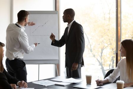 Two confident multiracial male employees standing near flipchart, presenting financial project positive results, discussing future steps for economic growth at business group meeting at office.