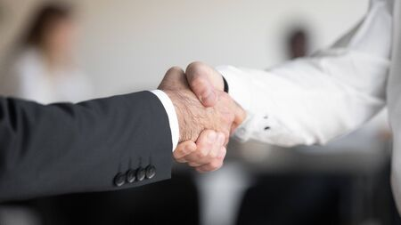 Close up cropped image two masculine businessmen hands shaking each other. Company male executive manager coming to agreement with corporate client. Team leader welcoming new employee at workplace.