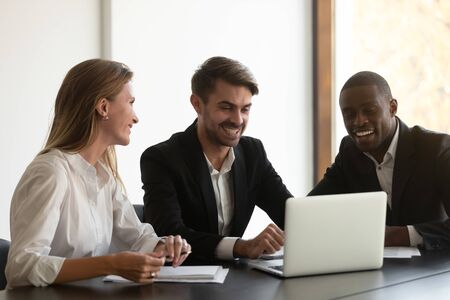 Happy mixed race business people sitting at table, looking at computer screen, satisfied with financial report, first project results. Smiling diverse colleagues having fun during break at office. Stock Photo