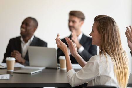 Side view head shot smiling young woman applauding to speaker, mixed race millennial colleagues team feeling joyful, celebrating great work results, company success at business meeting at office.