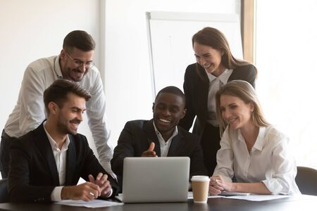 Positive african american male employee showing computer software to happy diverse coworkers at meeting. Young mixed race smiling manager explaining project results to cheerful teammates at office. Stockfoto