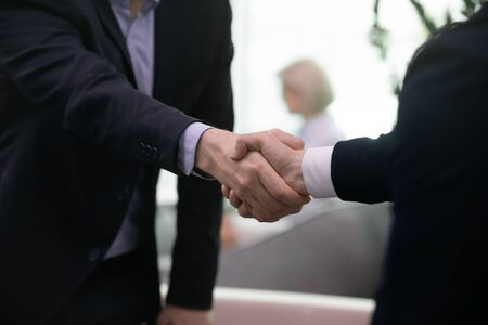 Close up of businessmen handshake getting acquainted greeting at office meeting, successful male business partners shake hands close deal after negotiation or briefing, partnership concept