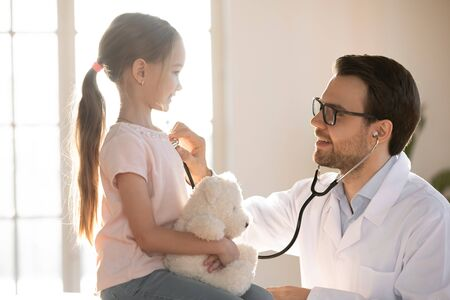 Side view pleasant professional male medical worker using stethoscope, listening lungs heartbeat of happy small preschooler at meeting in clinic. Little patient girl visiting pediatrician for checkup. Stock Photo