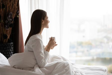 Side view happy attractive young brunette woman sitting in bed under duvet, holding cup of black coffee, enjoying peaceful calm weekend vacation morning time alone in bedroom at home or hotel.