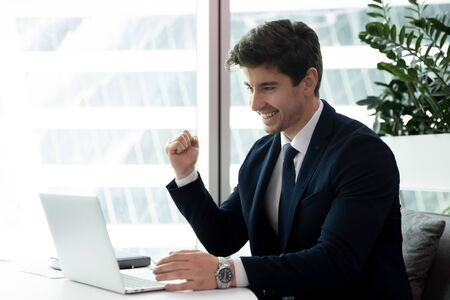 Overjoyed millennial male employee feel euphoric win online business lottery or grant on computer, happy young businessman triumph get good financial results statistics, reward, victory concept