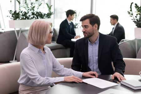 Diverse businesspeople sit at desk in office talk discuss partnership together, successful colleagues or business partners speak consider paperwork contract, close deal or make agreement at briefing