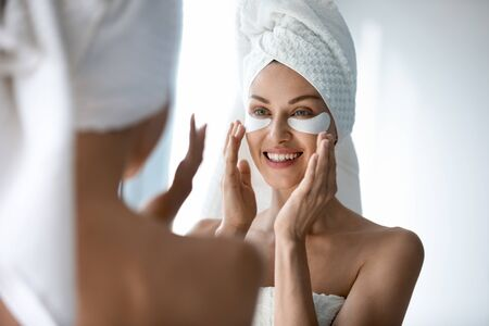 Head shot smiling pretty woman wearing towel applying hydrogel patches on under eye area, looking at mirror. Happy young lady enjoying morning antiage antiwrinkle routine in bathroom after showering.