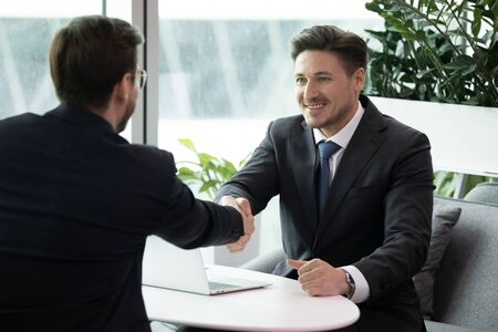 Happy male business partners shake hands get acquainted greeting at meeting in office, smiling businessman handshake close deal make agreement after successful negotiation, partnership concept Stockfoto