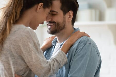 Close up happy loving couple touching foreheads with closed eyes, enjoying tender moment in modern kitchen together, smiling husband and young wife hugging, cuddling, romantic date at home