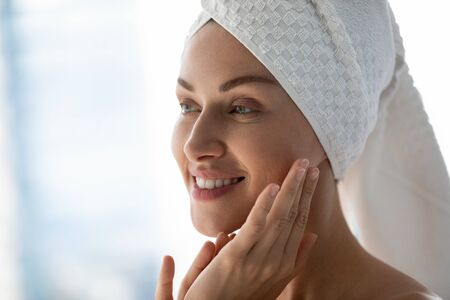 Close up head shot beautiful happy young woman with towel on head looking away in mirror, touching facial skin. Smiling attractive lady doing morning skincare routine in bathroom after showering.