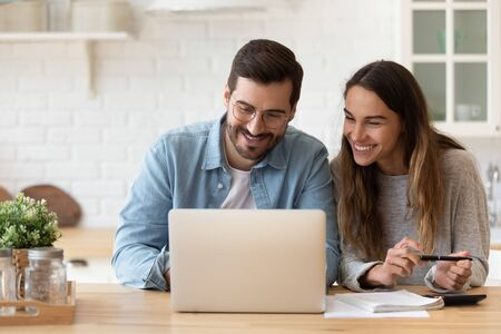 Happy young couple planning budget, reading good news in email, refund or mortgage approval, smiling woman and man looking at laptop screen, checking finances, sitting at table at home together Zdjęcie Seryjne