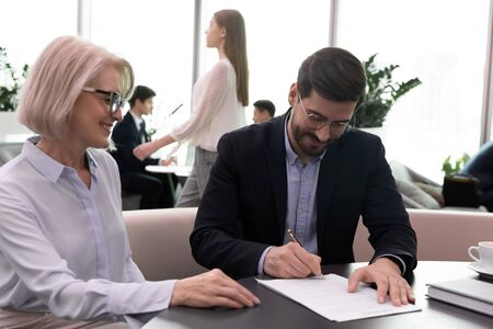 Excited male employee sign paper document after successful negotiation with business partner, happy businesspeople close deal put signature on paperwork make agreement at meeting, partnership concept Reklamní fotografie