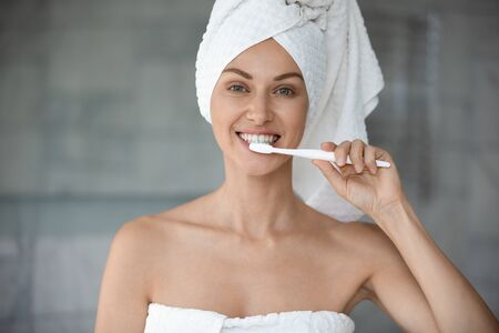 Smiling woman looking at camera, brushing teeth after showering, head shot close up. Happy healthy young lady feeling energetic after morning bath, using toothbrush, whitening teeth in bathroom.