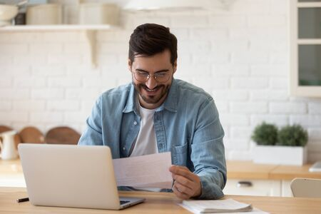 Excited young man wearing glasses reading good news in letter, sitting at table with laptop, happy satisfied male holding document, paper notification, job promotion, loan approval, great exam result