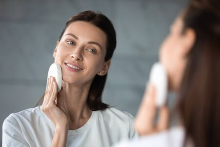 Pleasant attractive brunette woman looking at mirror, removing makeup in evening at bathroom. Head shot close up young lady cleansing skin, enjoying grooming routine, exfoliating face with sponge. Фото со стока