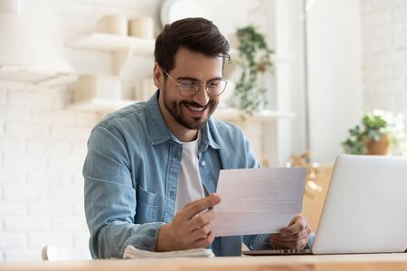 Smiling young man reading good news in paper notification, sitting at table with laptop, happy satisfied male wearing glasses holding document, job promotion, loan approval, great exam result Archivio Fotografico