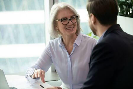 Smiling middle-aged female employee talk brainstorm with male colleague at office briefing in boardroom, happy diverse coworkers have fun laugh cooperating discussing ideas at meeting Imagens