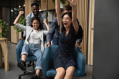Excited businesswomen riding on chairs, laughing and shouting, diverse colleagues having fun in office, happy employees enjoying funny game during break, celebrating business success or achievement