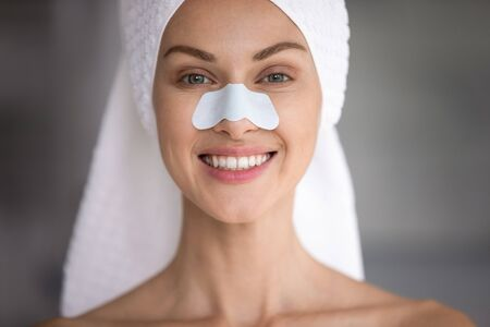 Close up head shot happy attractive lady with cleansing strip on nose looking at camera. Portrait of groomed young beautiful woman with towel on wet hair feeling excited about domestic spa procedures.