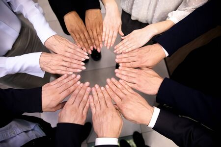Close up top view of multiracial colleagues join hands in circle show unity and support at work, diverse multiethnic employees engaged in creative teambuilding activity or training in office Фото со стока