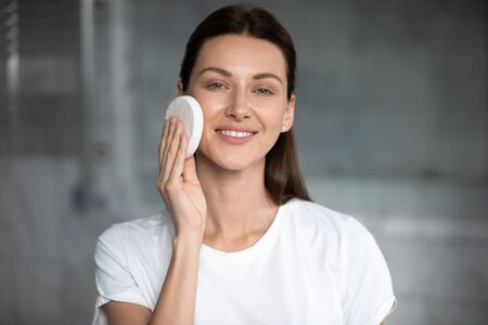 Head shot close up portrait young attractive woman looking at camera, removing makeup or cleansing exfoliating healthy face skin with sponge, skincare treatment daily evening routine concept.