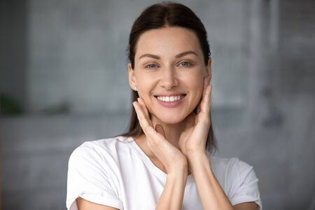 Head shot close up young pretty smiling woman touching cheeks, satisfied with good skin condition, looking at camera. Portrait of happy groomed attractive lady, satisfied with cosmetology services. Reklamní fotografie