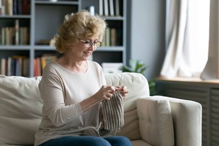 Happy middle-aged woman sit on sofa in living room hold needles knitting at home, relaxed elderly grandmother enjoy domestic weekend engaged in favorite hobby activity, retired wellness concept