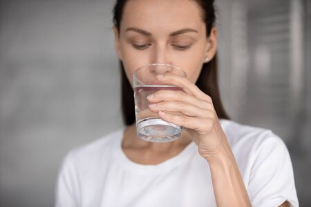 Focus on peaceful young brunette woman drinking glass of fresh aqua, head shot close up. Attractive 30s lady sipping water, enjoying daily healthcare routine, every day healthy habit concept.