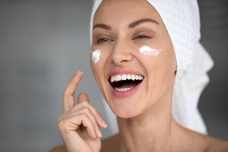 Overjoyed laughing young pretty woman with towel on head applying moisturizing creme on cheeks, feeling energetic after morning shower. Happy lady grooming herself in bathroom, skincare routine.