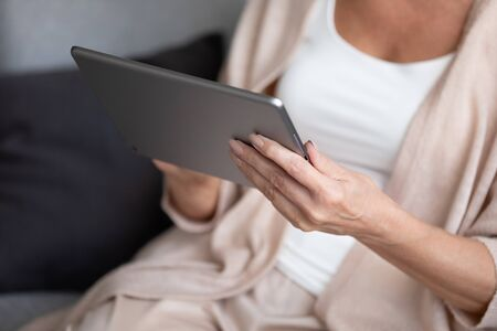 Close up mature woman holding digital tablet. Older retired lady using computer applications, chatting with friends in social networks, shopping in internet store, reading e-book or news in media.