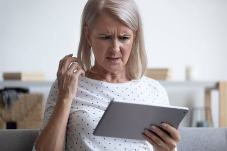 Frowning middle aged woman looking at computer tablet, irritated by spam email or bad gadget work, head shot. Displeased elder generation female user annoyed by poor internet connection or malware. Foto de archivo