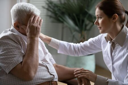 Young nurse spend time with old man, shares his pain, express empathy caring about 80s patient provide psychological support listens his life health complaints in diseases, relieves loneliness concept Stock fotó