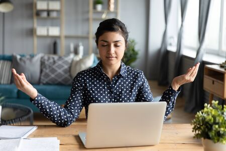Calm Indian woman with closed eyes meditating at workplace, peaceful mindful young female sitting at desk in modern living room, practicing yoga during break, relieving stress, negative emotions