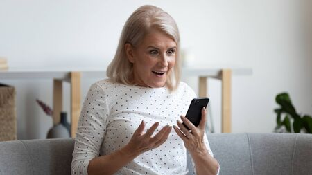 Excited mature woman holding mobile phone, received message with unexpected good news, sitting on couch at home. Happy middle aged grandma reading online lottery win email notification in smartphone.