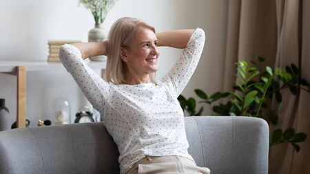 Pleasant smiling middle aged woman relaxing on cozy coach in modern living room, looking away. Happy older lady dreaming, visualizing future, resting, enjoying weekend free leisure time alone at home.