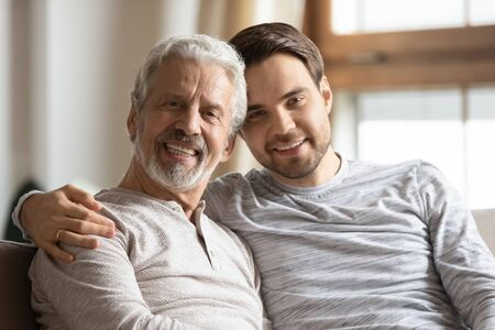 Headshot portrait of happy young man hug cuddle elderly father relaxing at home together, smiling mature dad parent embrace grown-up adult son enjoy family weekend reunion, bonding concept