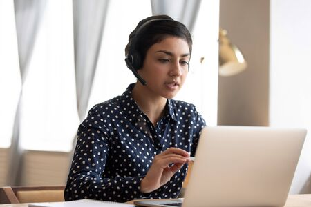 Serious Indian woman wearing headphones with microphone talking, using laptop, looking at screen, young female consulting client, video call, student learning language online, listening lecture