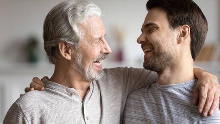 Glücklicher junger Mann umarmt älteren Vater viel Spaß beim gemeinsamen Genießen des Wochenendes zu Hause, lächelnder reifer Vater umarmt erwachsenen erwachsenen Sohn, zeigt Stolz und Unterstützung, Familienbindung, Eltern-Kind-Beziehungskonzept