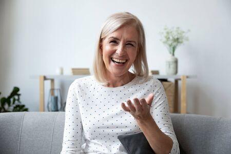 Fröhliche reife blonde Dame, die auf der Couch sitzt, Videoanruf mit Freunden hält, Kopfschuss Nahaufnahme Porträt. Webcam-Ansicht lachende Frau mittleren Alters, die Spaß hat und online mit erwachsenen Kindern spricht.